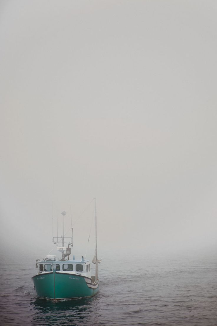 A lobster boat chugs slowly towards the camera through thick fog