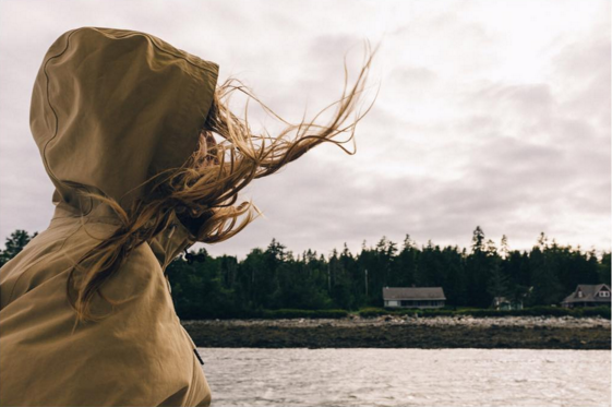 A woman in a hooded rain jacket looks towards a rocky Maine shore as her hair is blown by the wind