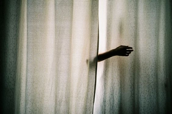 A seemingly disembodied arm reaches out from between two curtains