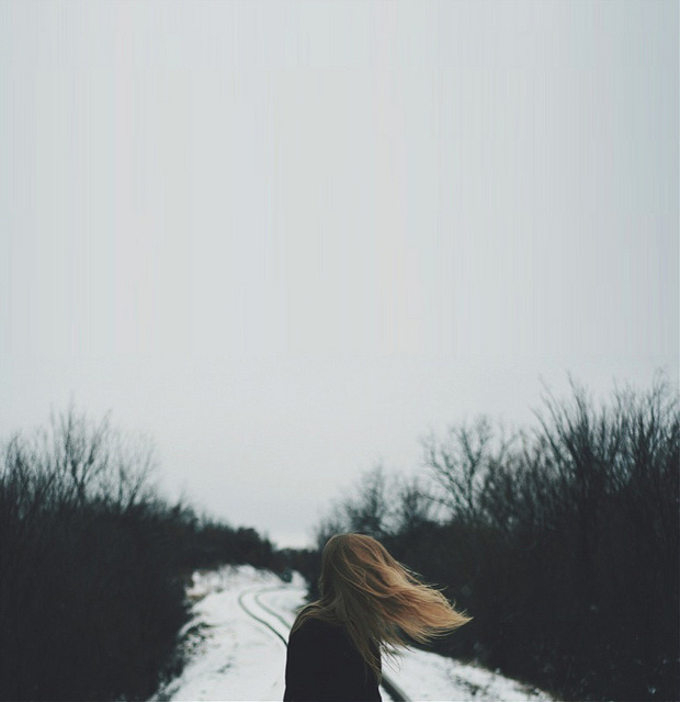 A woman looks back at a snowy path as the wind blows her hair